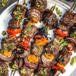 grilled steak and veggie skewers with a jalapeno parsley chimichurri sauce on a white plate, pin image