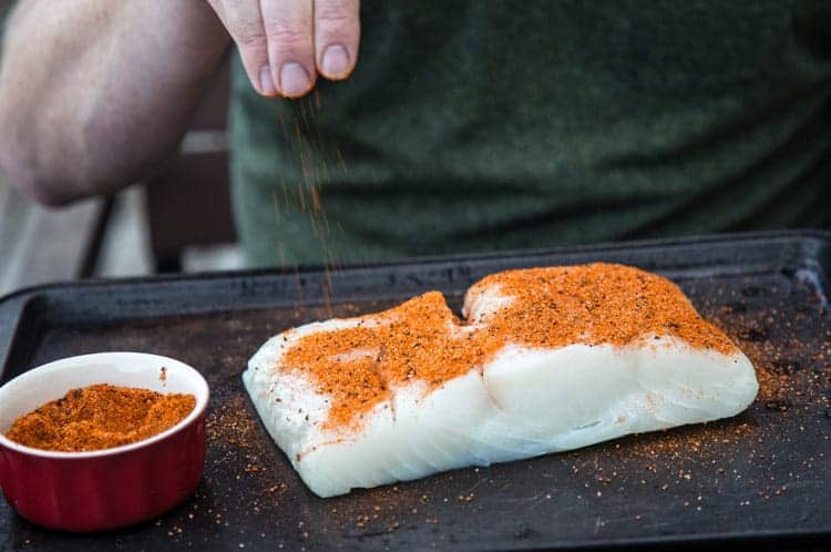 A large piece of white fish being sprinkled with homemade seafood seasoning