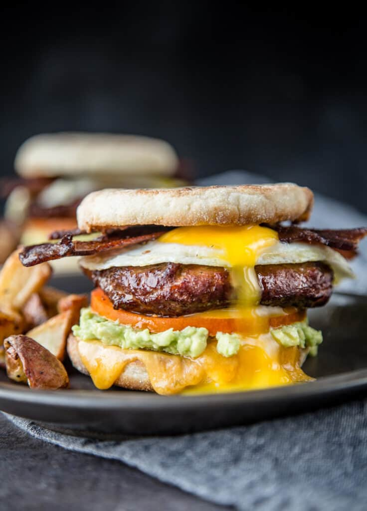 A Breakfast Sandwich topped with Smoked Sausage, an over easy egg, and smoked bacon.