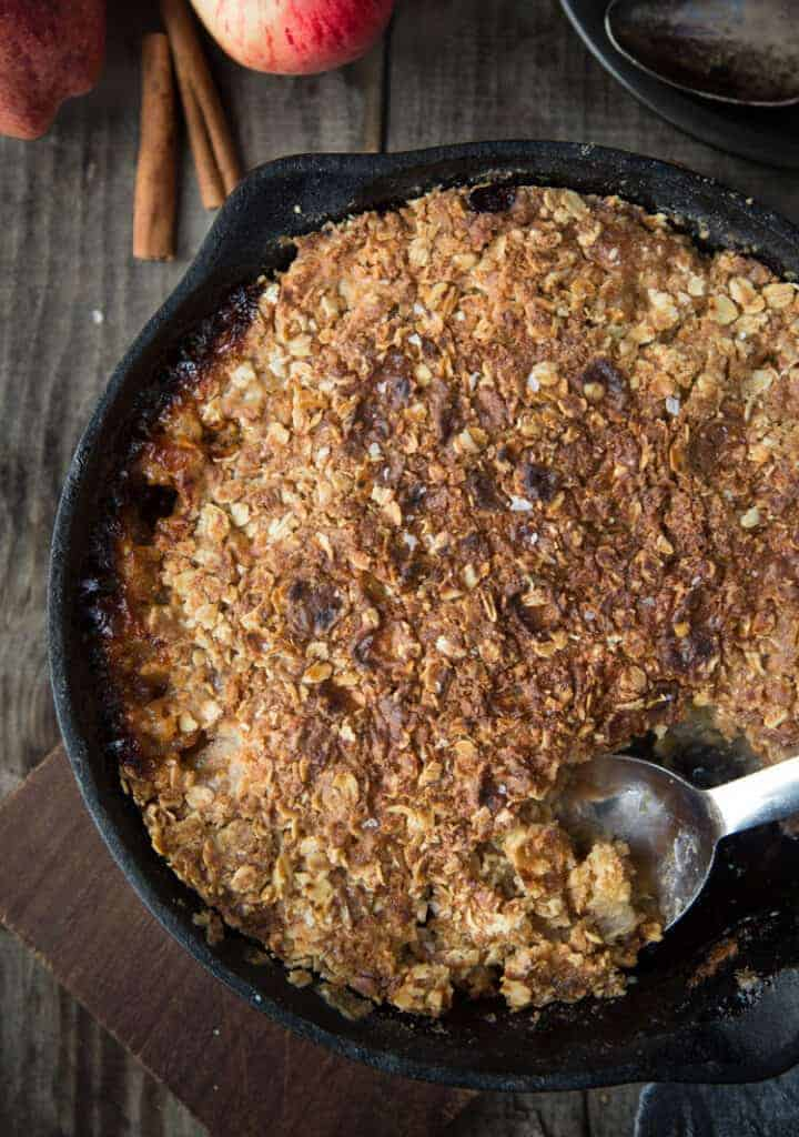 Grilled Apple Crisp in a cast iron with a scoop taken out