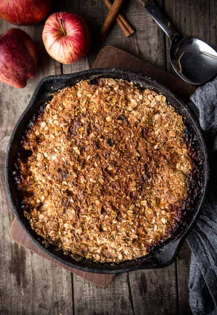 grilled dessert in a cast iron pan with apples and cinnamon to the side