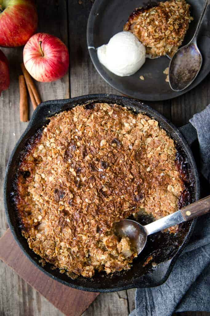 Grilled Apple Crisp in a black pan with a plate of apple crisp and ice cream to the side
