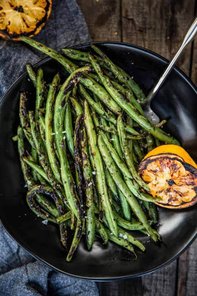 Grilled Green Beans on a black plate with grilled lemon to the side
