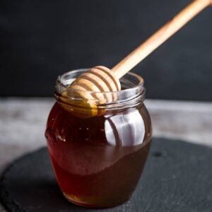Smoked Honey in a mason jar with a wood honeycomb stick
