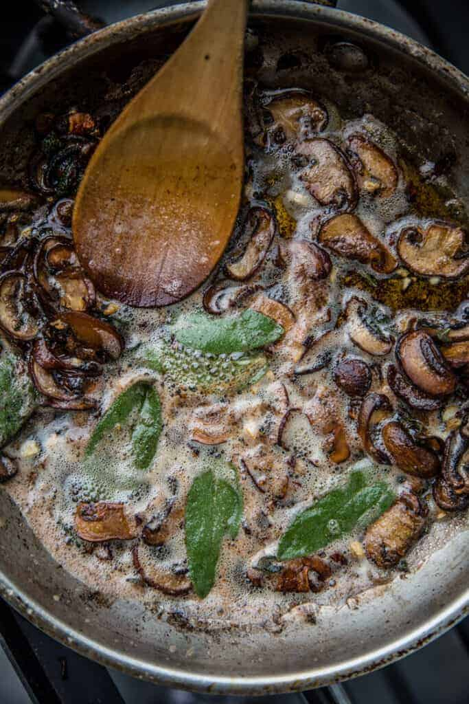 A skillet filled with butter sauteing mushroom and sage.
