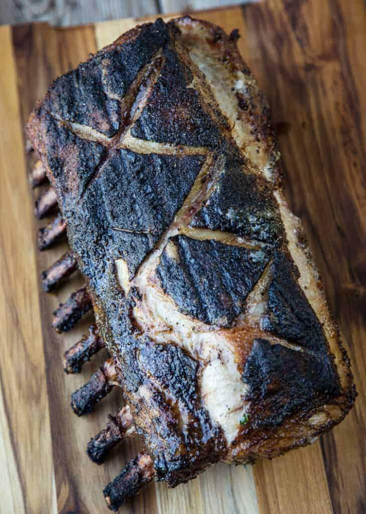 Grilled bone-in pork roast on a cutting board