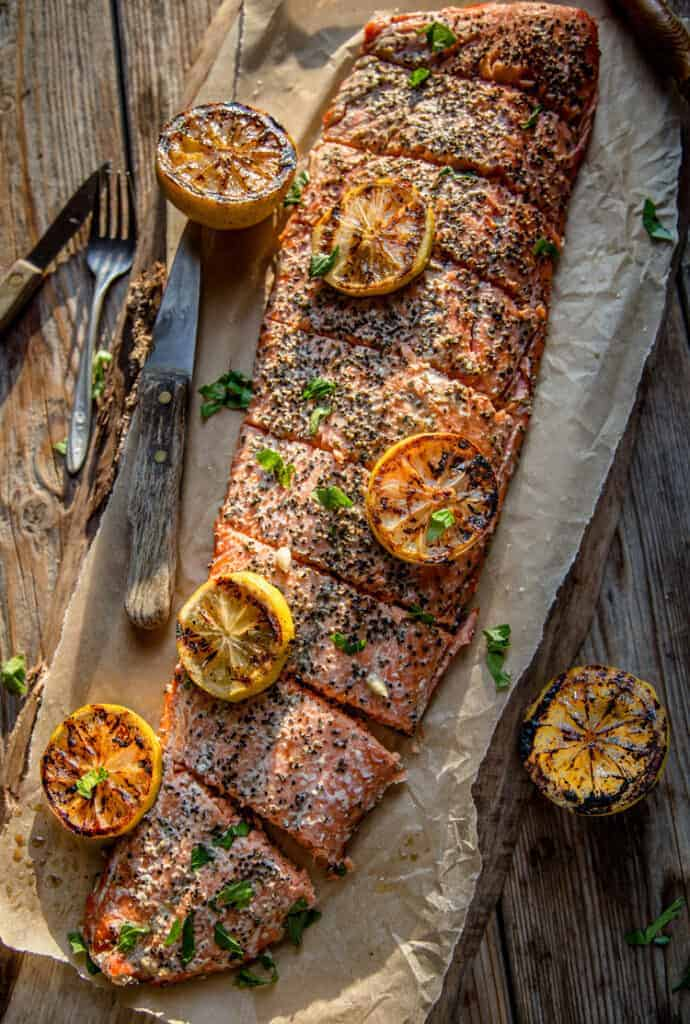 Whole hot smoked salmon filet on a wood board resting