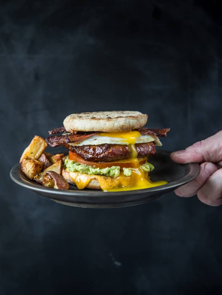 A Breakfast Sandwich with Smoked Sausage and Bacon on a plate.
