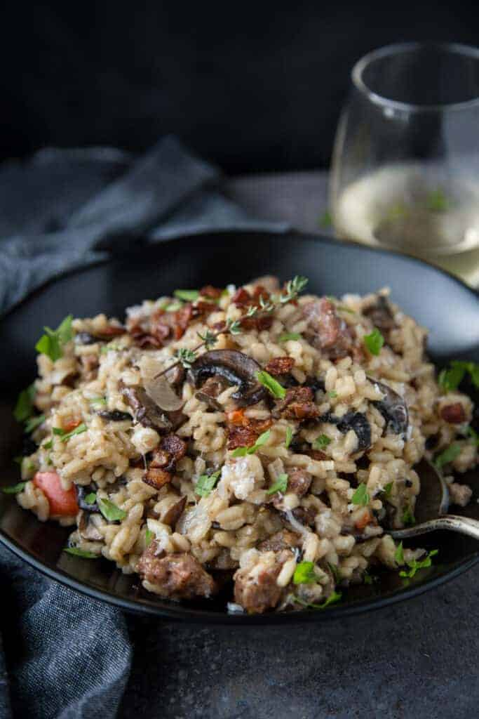 A bowl of homemade risotto with smoked sausage, mushrooms, and bacon, paired with a glass of wine.