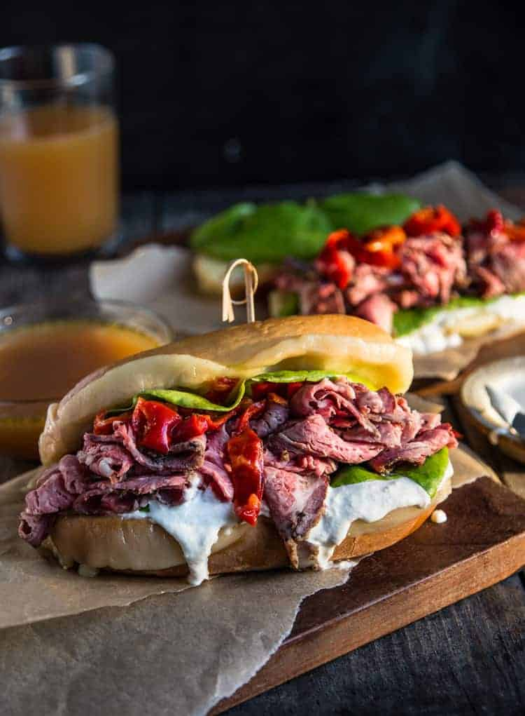 french dip sandwich with cheese, peppers, and sauce