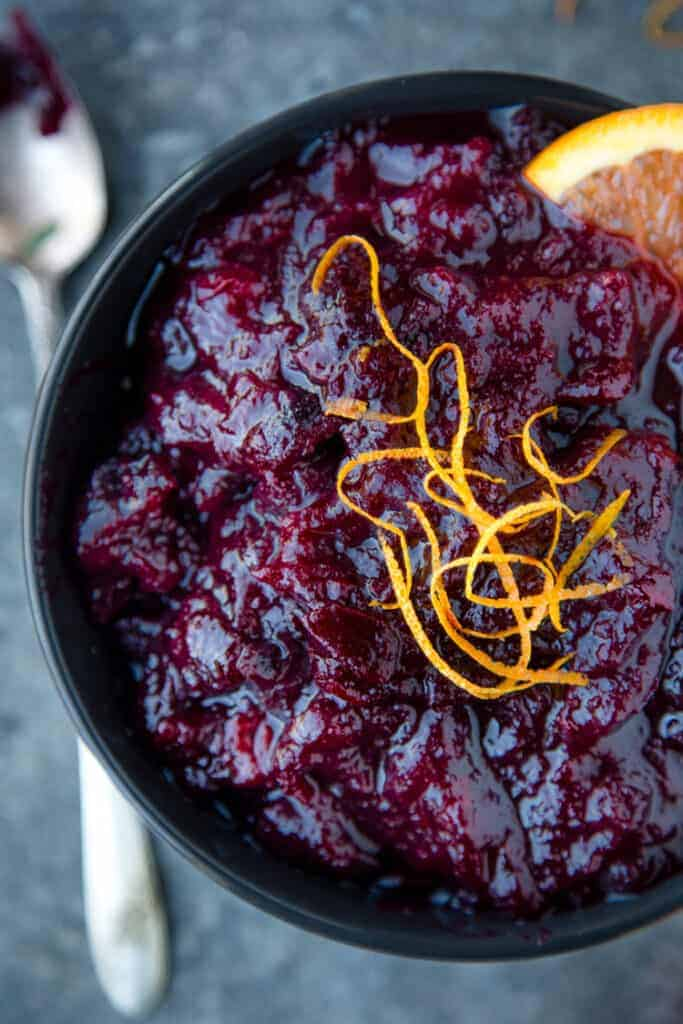 A bowl of Homemade Red Wine Cranberry Sauce with orange zest on top