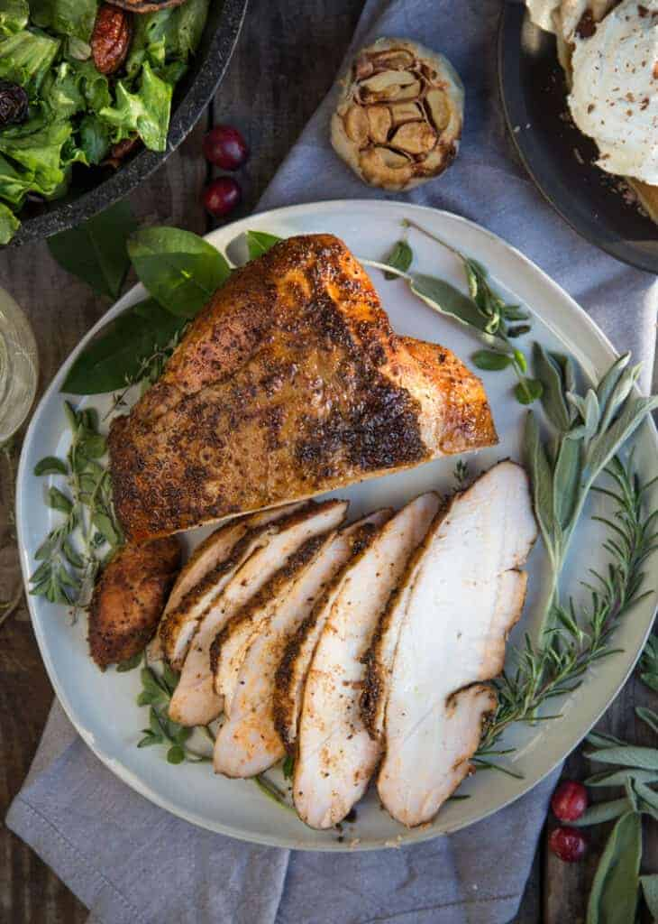 Smoked Turkey Breast on a plate with other Thanksgiving side dishes.