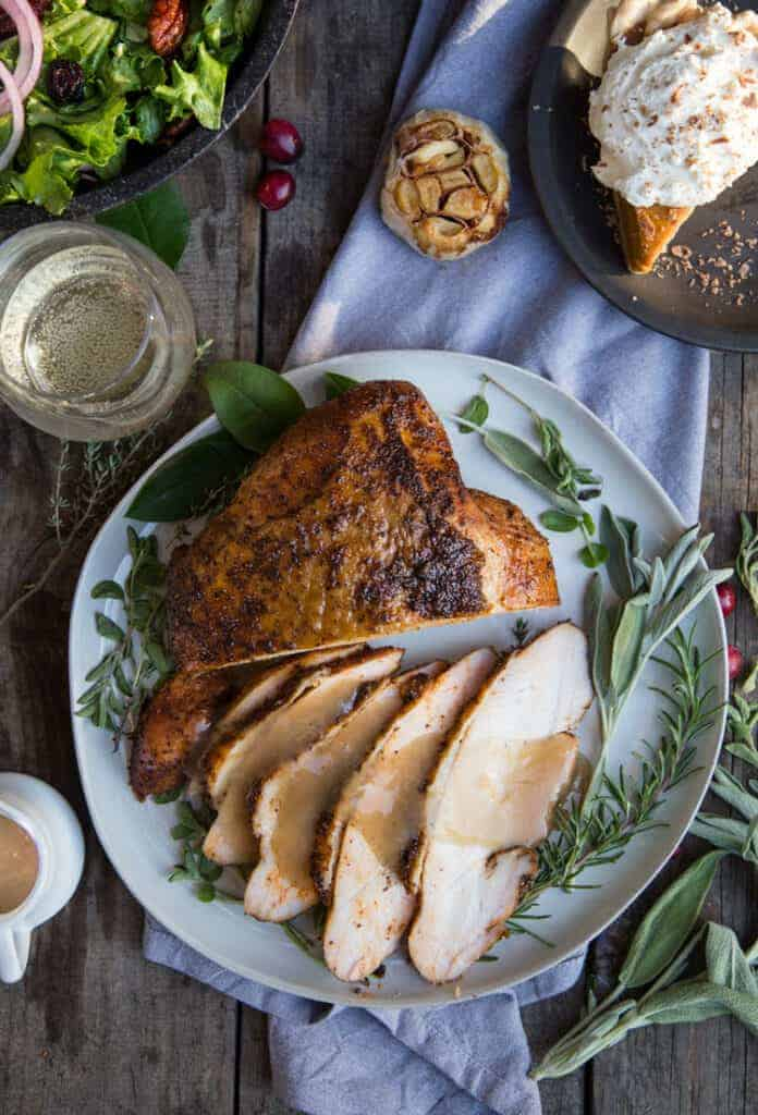 Smoked Turkey Breast on a plate with other Thanksgiving side dishes and a glass of wine.