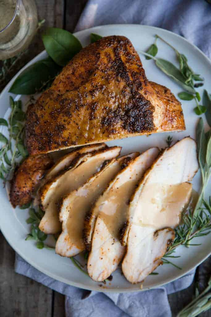 Smoked Turkey Breast sliced on a plate with smoked gravy drizzled over the top.