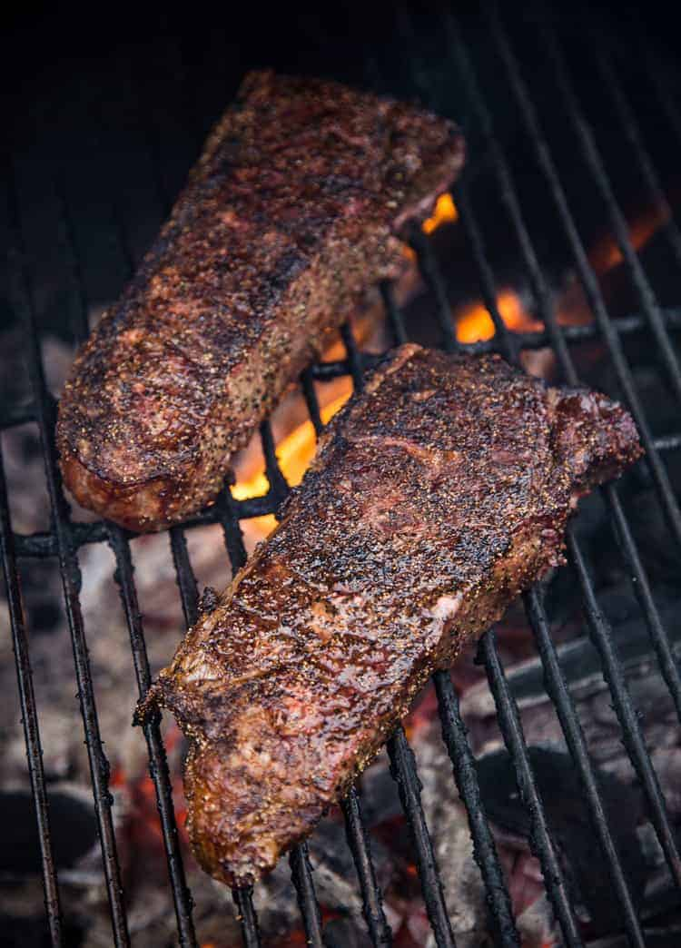 NY Strip steaks being grilled with two-zone grilling.
