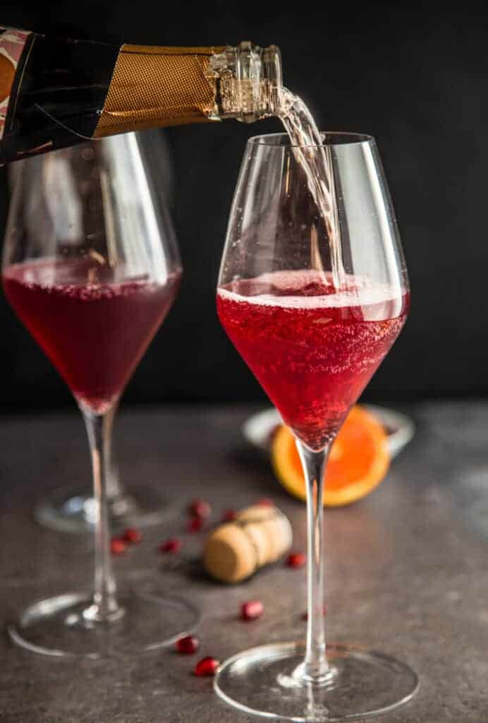 Pomegranate Mimosas being made with Cava sparkling wine.