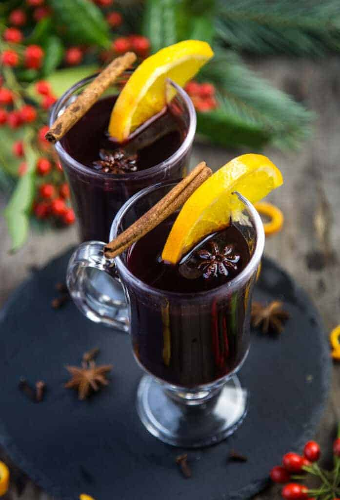 Mulled Wine holiday cocktail in a glass garnished with star anise and orange.