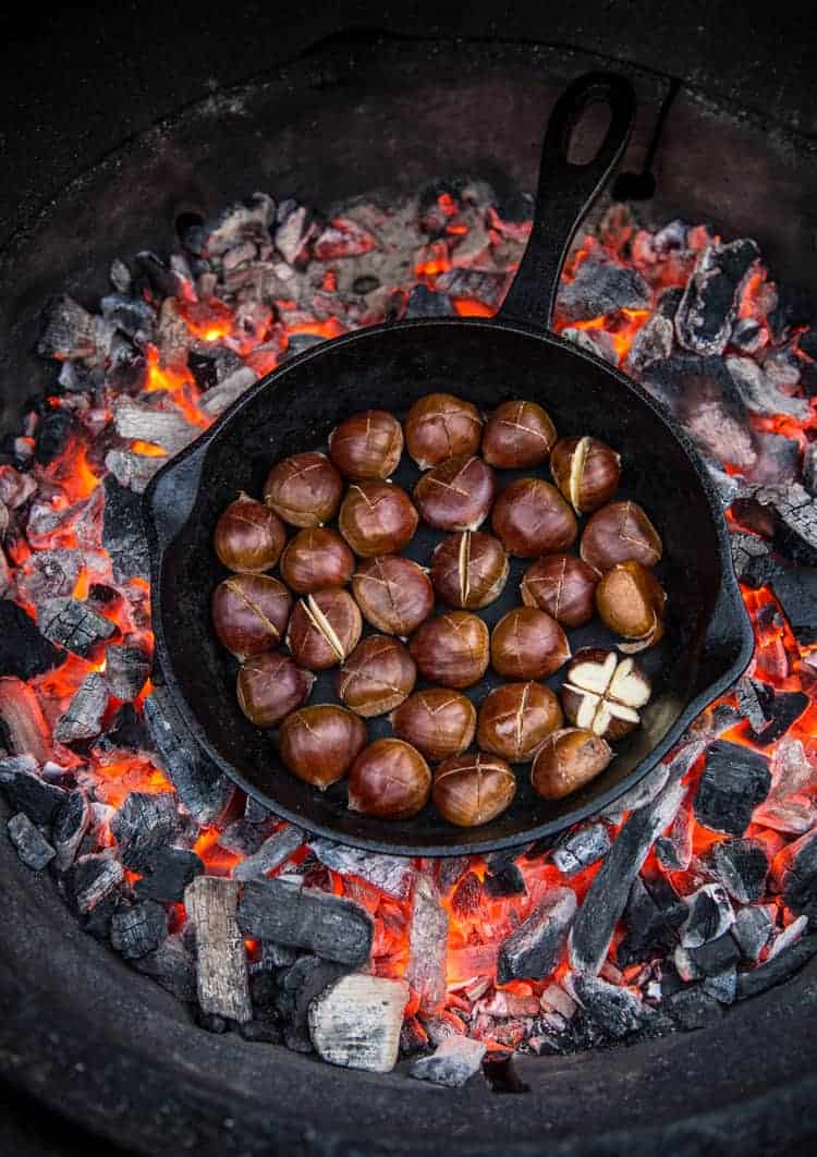 Roasted chestnuts in a cast iron skillet in a fire pit