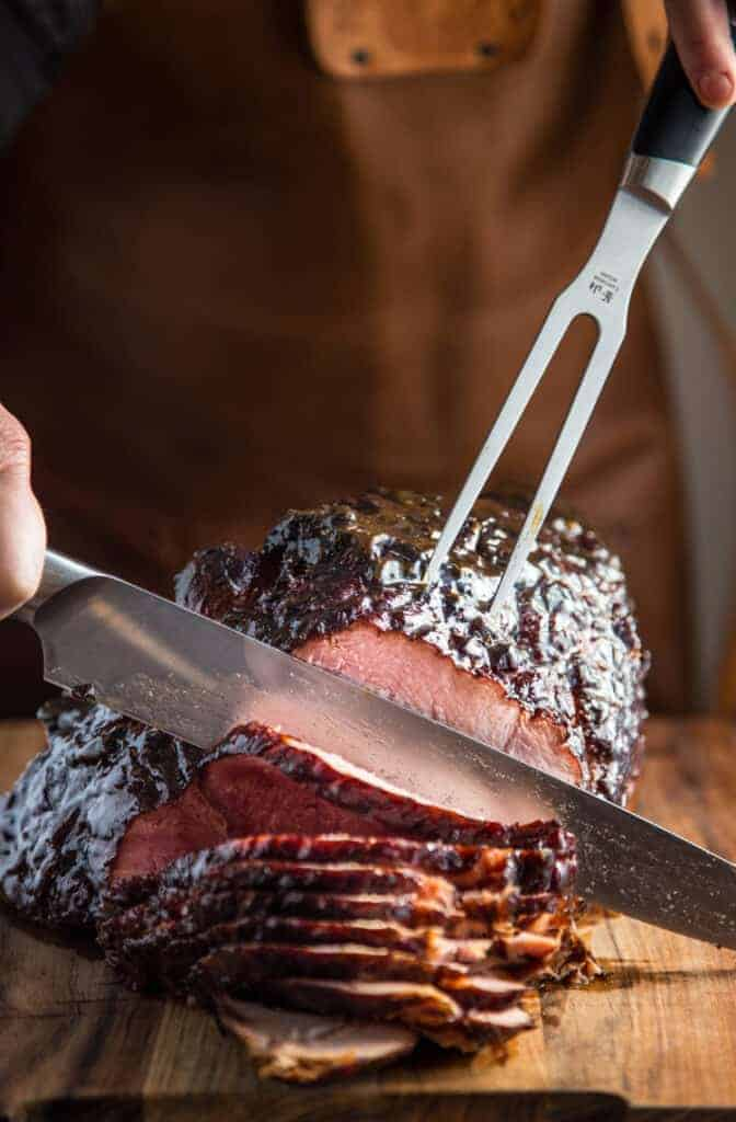 Slicing smoked ham after the brown sugar glaze has set.