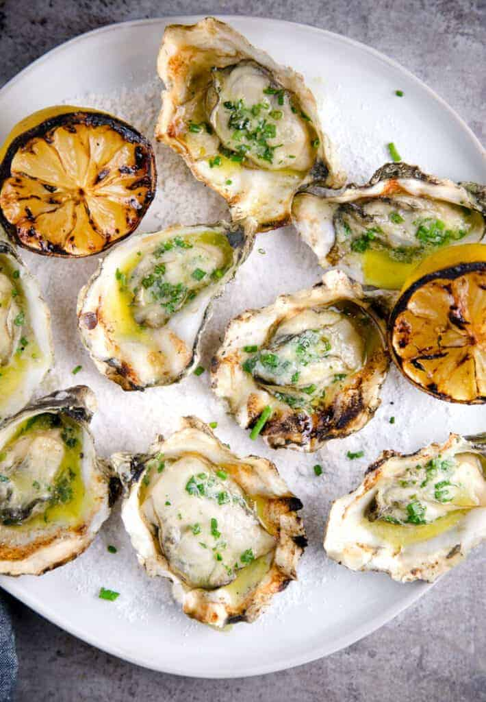 A plate of grilled oysters and grilled lemons