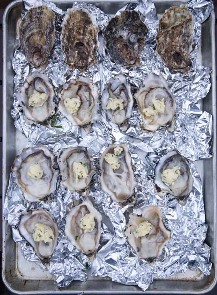 A baking sheet of open oysters topped with a white wine butter, ready for the grill