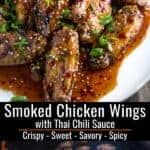 Smoked chicken wings on the smoker and glazed with a Thai Chili Sauce and garnished with sesame seeds and green onions pinterest text
