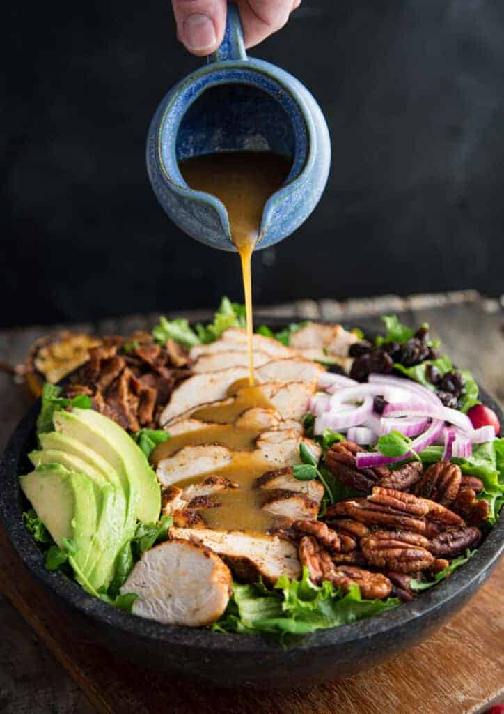 Dressing poured over a grilled chicken salad recipe