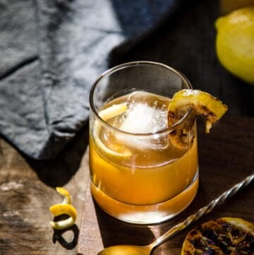 Bourbon cocktail garnished with grilled lemon