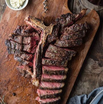 A Grilled T-Bone Steak sliced up and served with a glass of wine