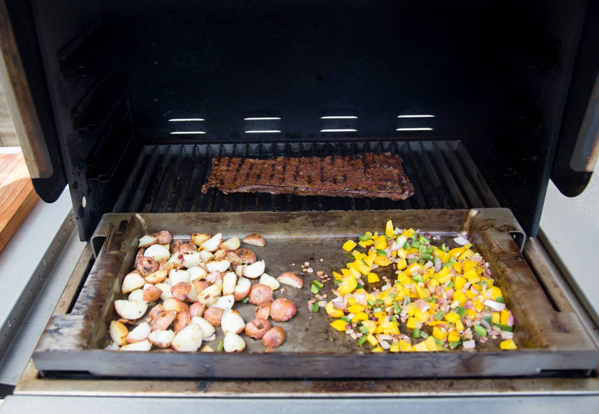 Vegetables and steak cooking on the grill at the same time, preparing for breakfast burritos.