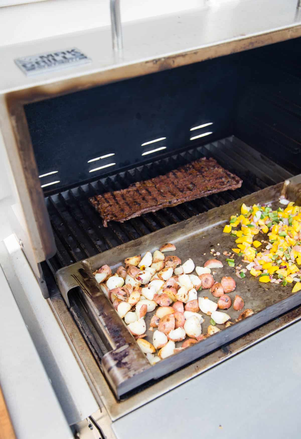 A grill with a skirt steak cooking in the back and potatoes and vegetables cook on a hot griddle in the front