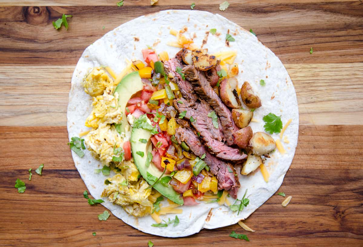 An open faced breakfast burrito filled with steak, vegetables, and eggs before being wrapped.