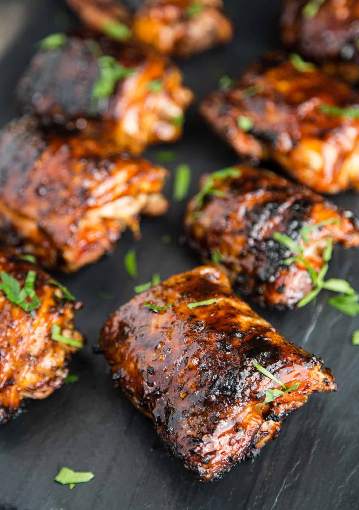 A closeup of grilled chicken thighs on a black platter after being topped with BBQ sauce