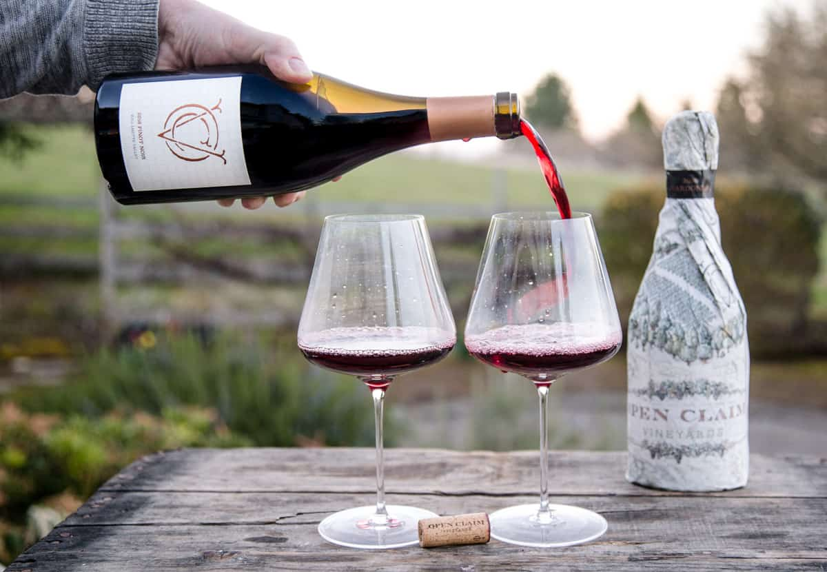 Pouring a bottle of Open Claim Pinot Noir into two wine glasses on a wooden board