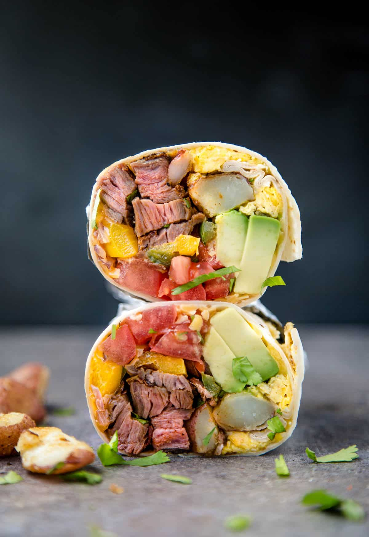 A burrito filled with steak, vegetables, and eggs, cut in half.