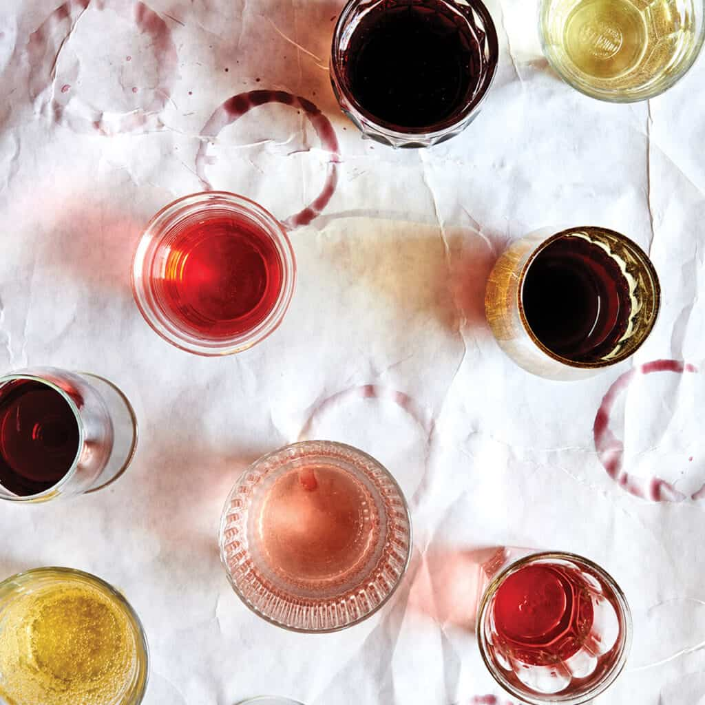 A top down photo of different glasses of wine, taken from Dina Avila for the Fire and Wine cookbook