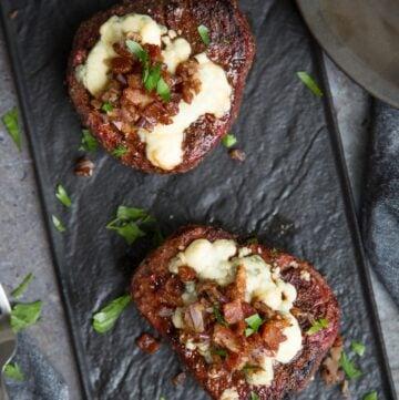 Two Grilled Filet Mignon Steaks on a black platter