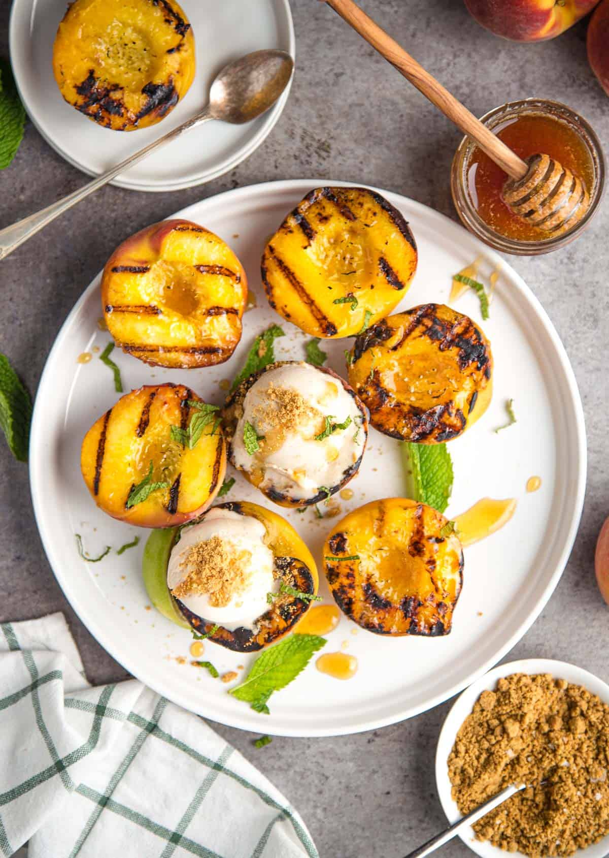 A platter of grilled peaches topped with ice cream and smoked honey