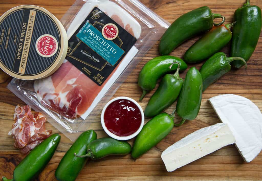 Ingredients for jalapeno poppers with brie cheese and prosciutto on a wood cutting board