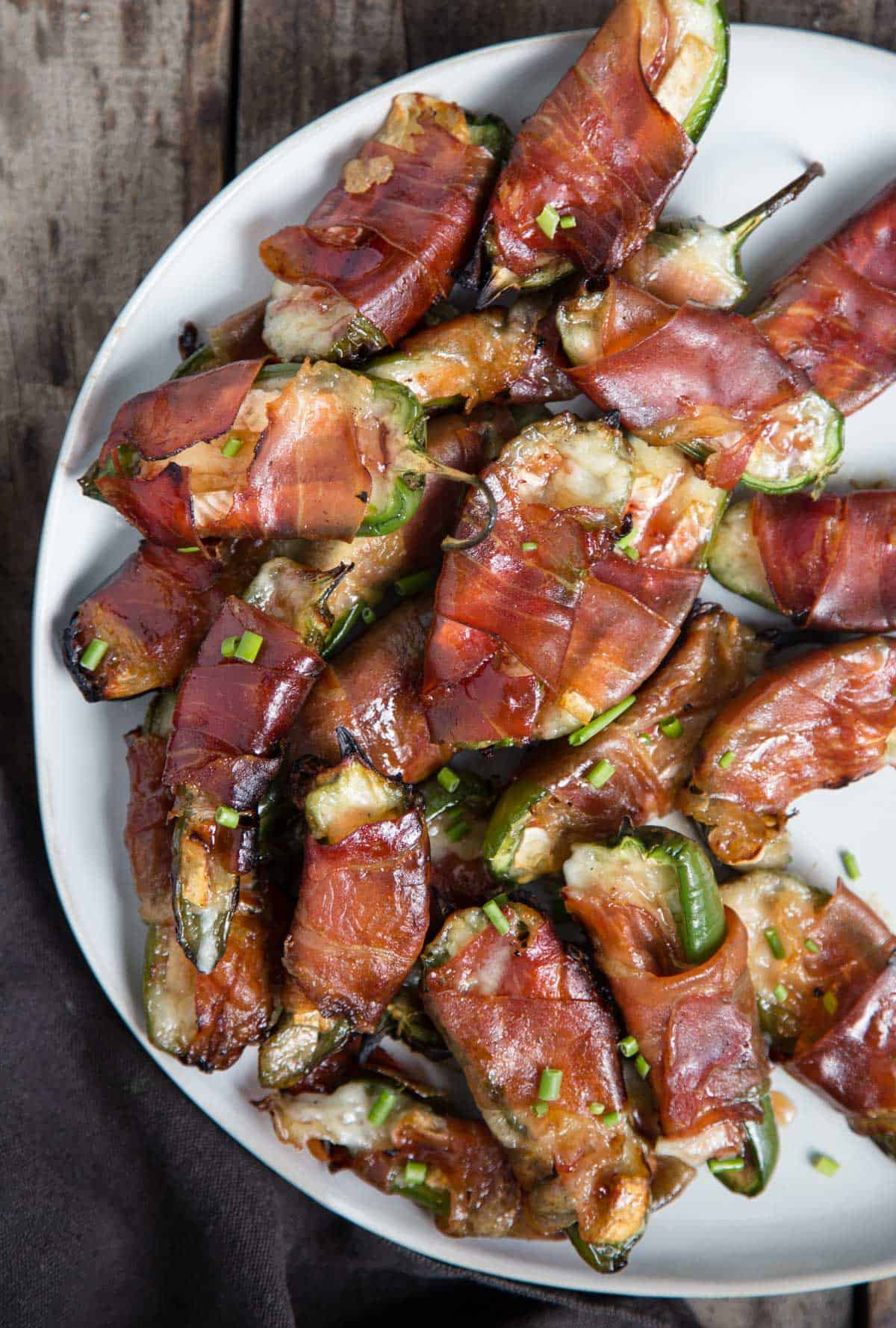 A platter of jalapeño poppers stuffed with brie cheese and wrapped with prosciutto on a white plate