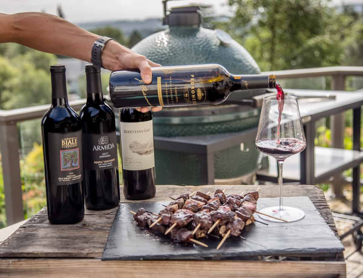 A bottle of Zinfandel being poured into a glass near a plate full of grilled beef skewers.