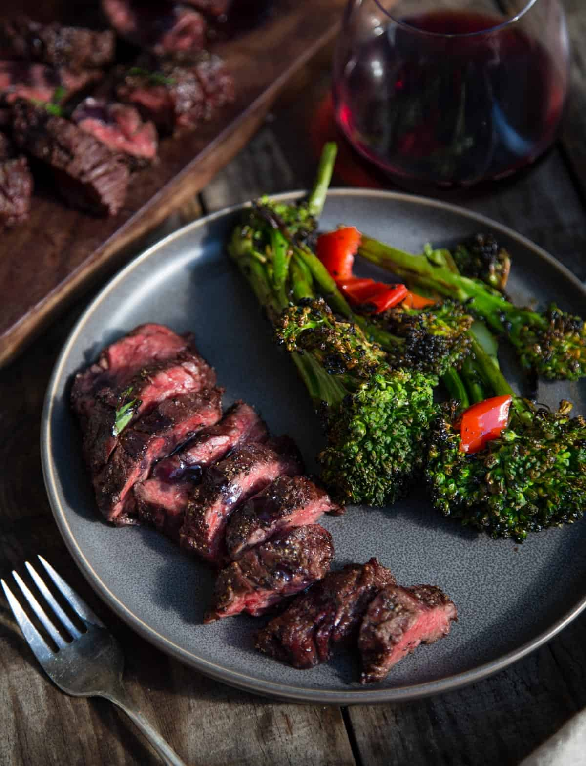 A plate with grilled beef and a side of broccolini