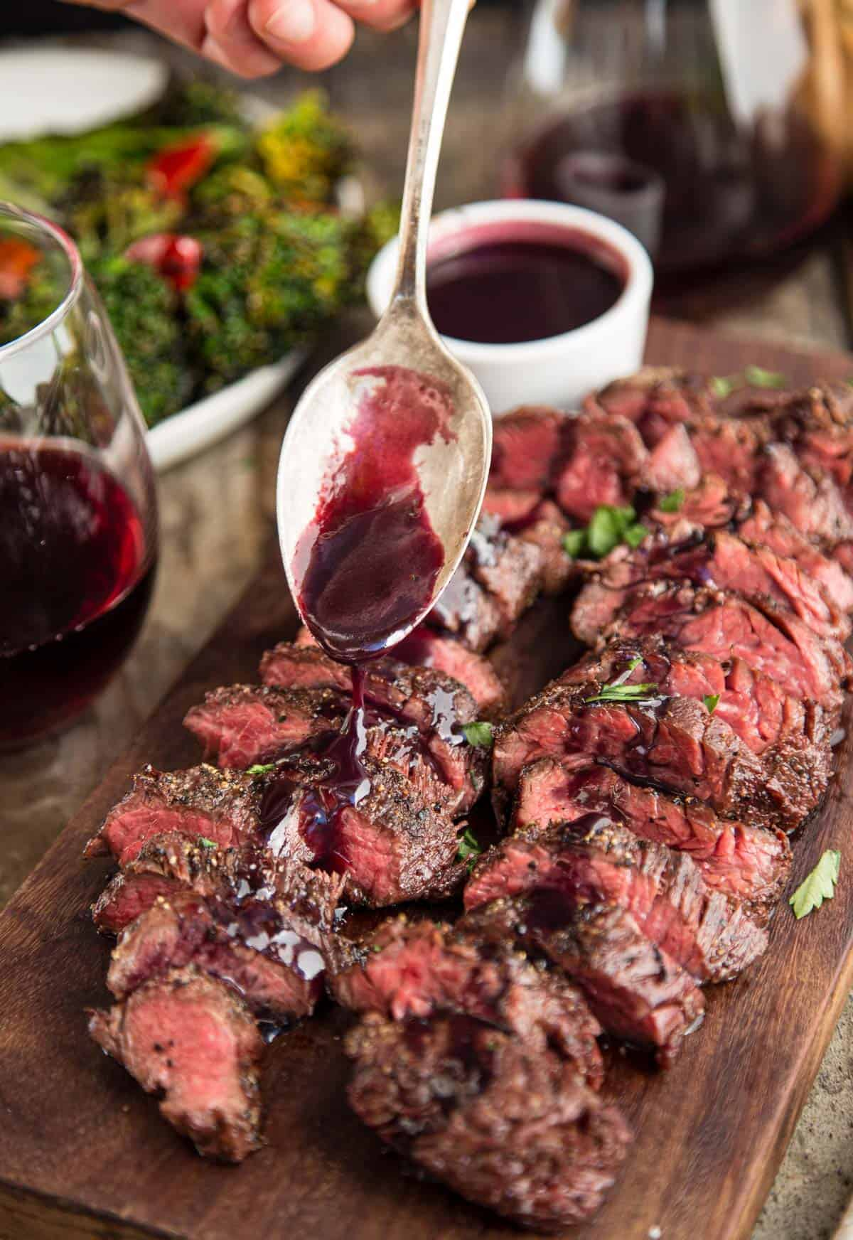 Slices of Grilled Hanger Steak with a wine reduction sauce being poured over the top