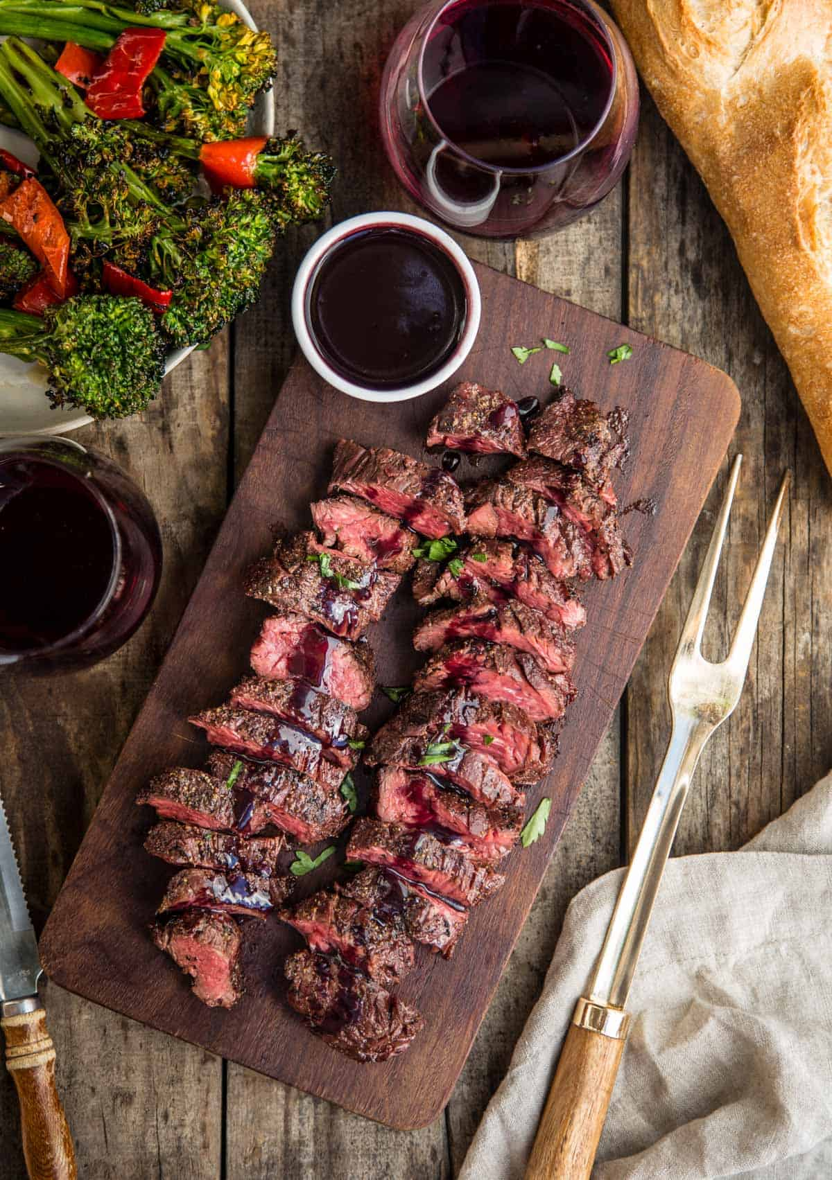 Grilled Hanger Steak on a wood serving platter covered in a wine reduction sauce and two glasses of wine