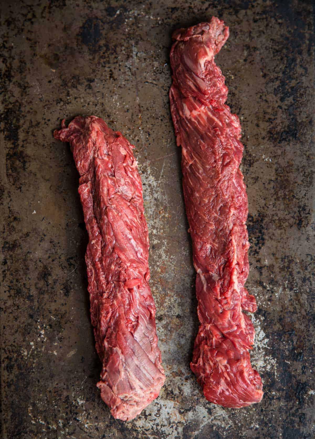 Two raw hanger steaks on a platter
