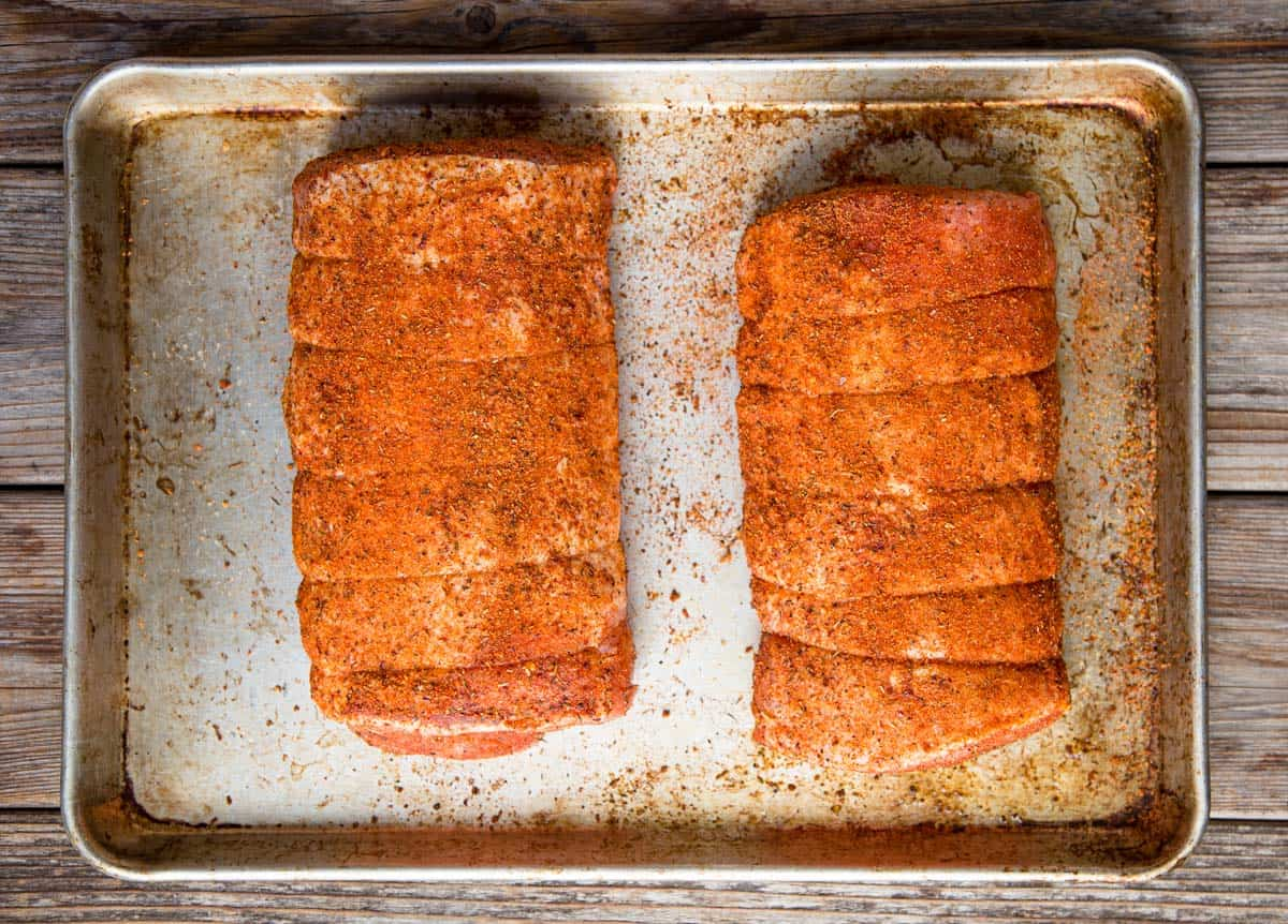 A raw pork loin coated with seasoning