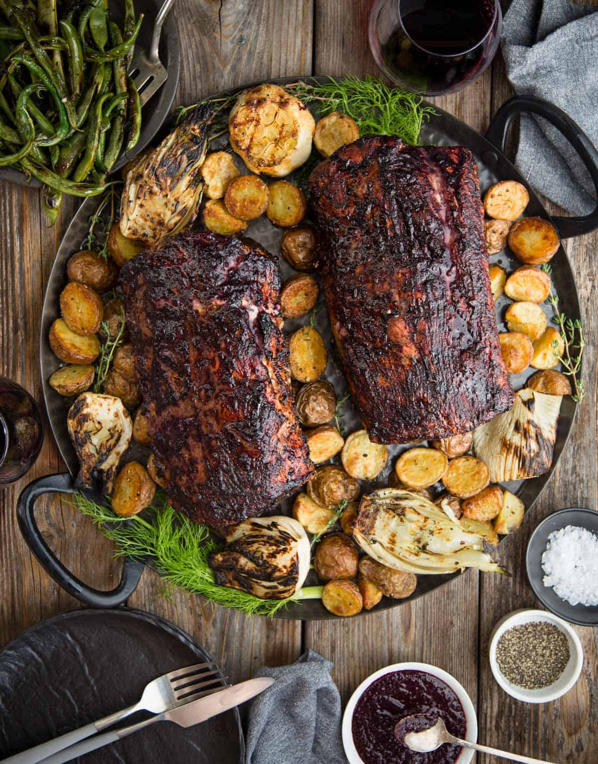Two Grilled Pork Loins on a platter with roasted vegetables