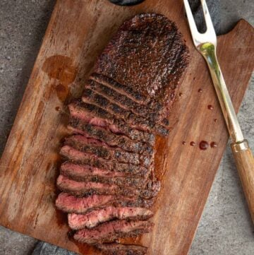 Flat iron steak grilled and sliced on a cutting board.