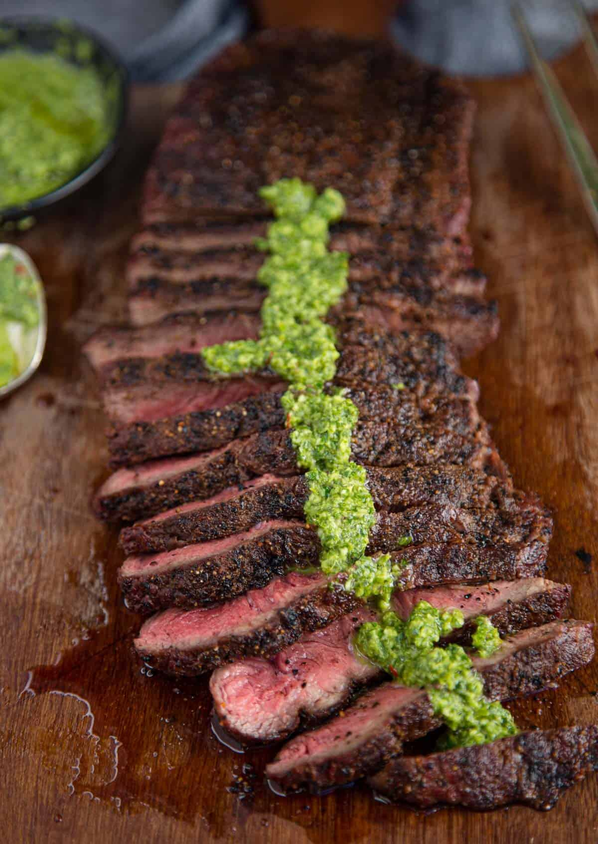 Slices of grilled flat iron steak topped with chimichurri sauce.