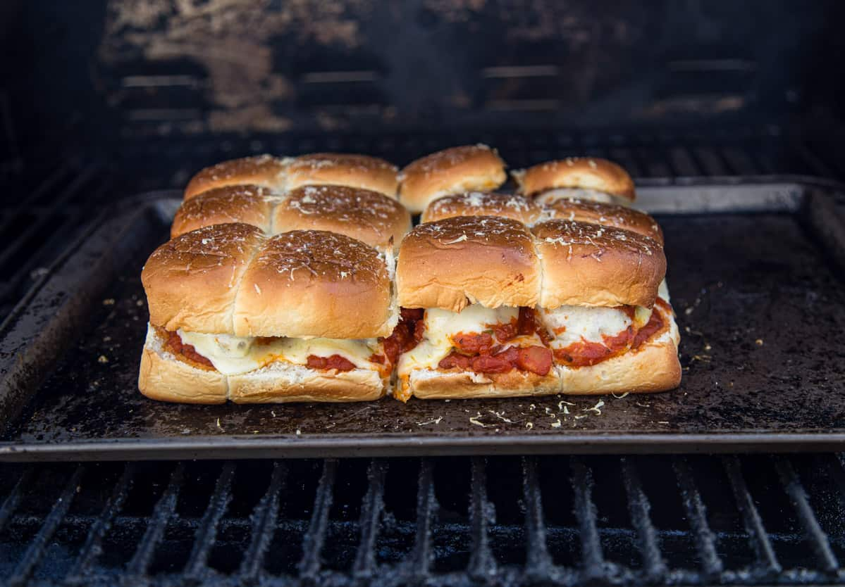 A sheetpan with meatball sliders cooking on the grill